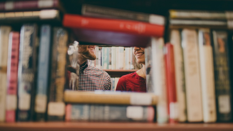 Man and woman smiling at one another surrounded by books.