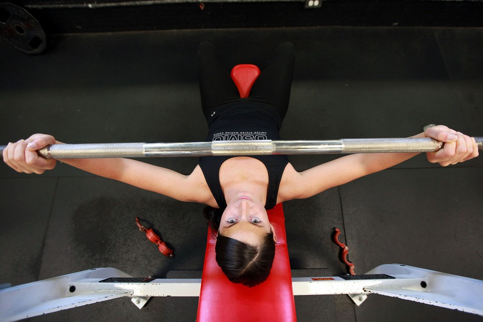 Woman lifting weights at an on-site/at-home fitness center.